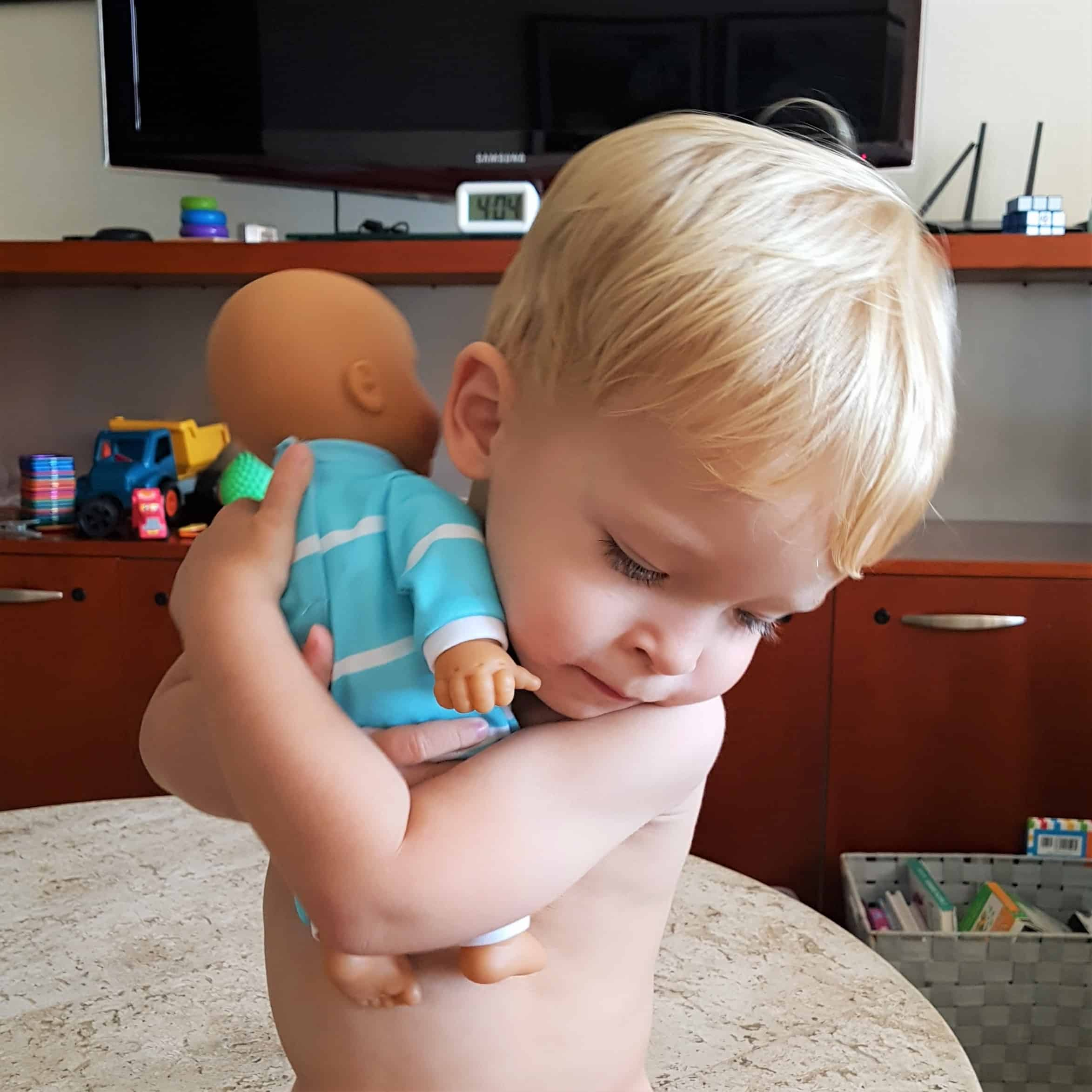 image of toddler boy hugging doll
