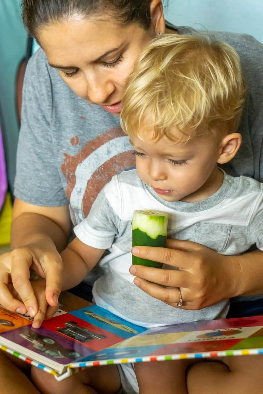 toddler and mom reading eating cucumber