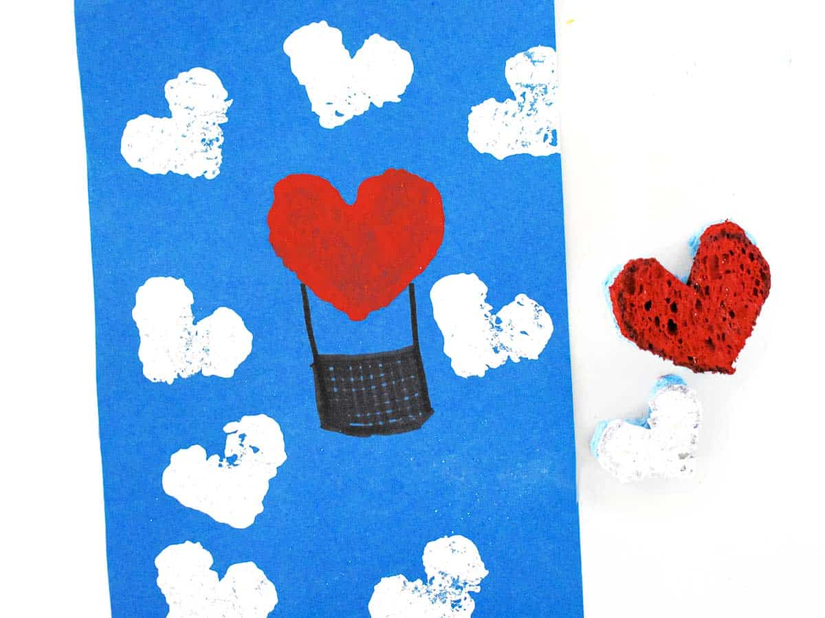 heart stamped hot air balloon next to heart-shaped sponge dipped in paint