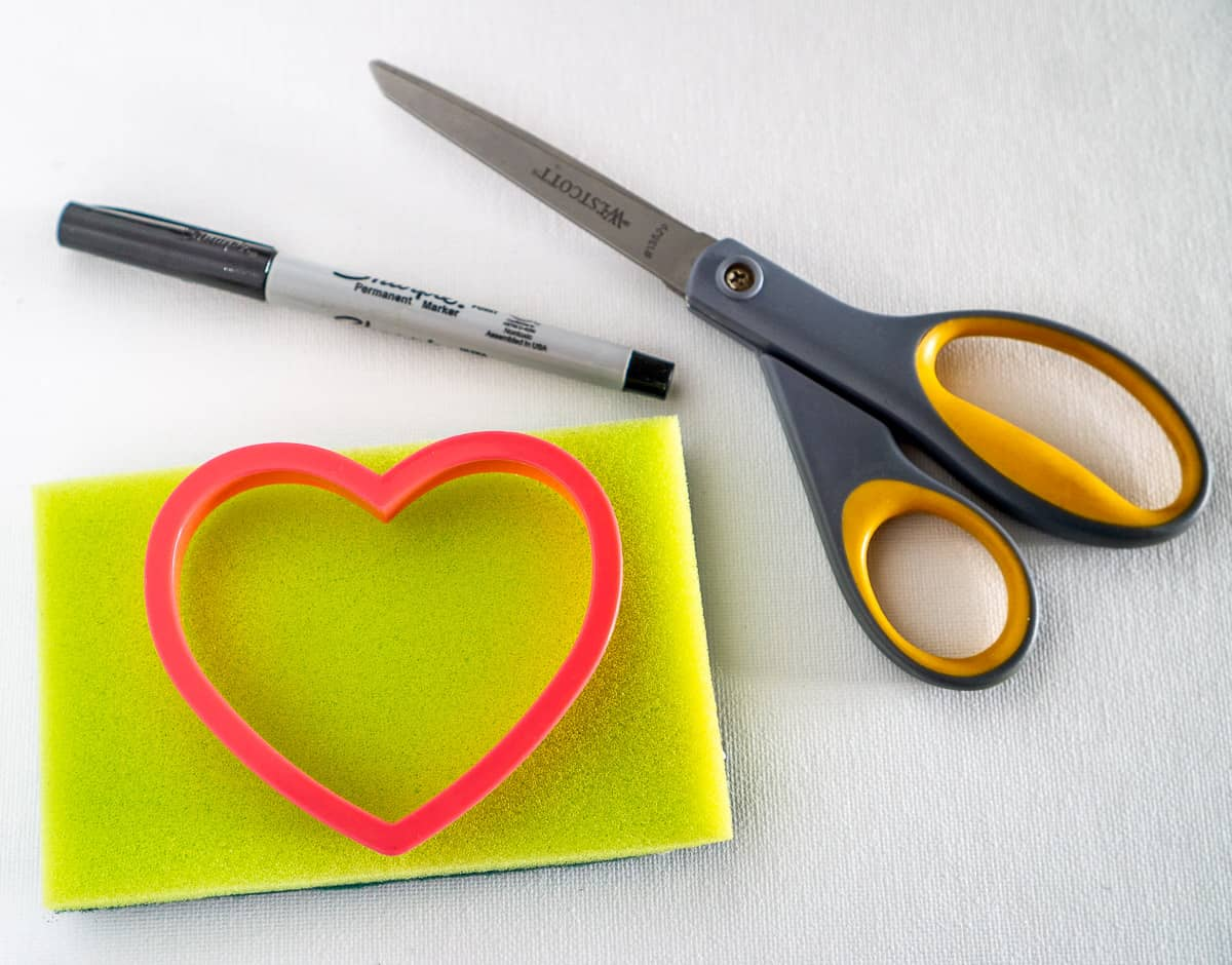 sponge, scissors, cookie cutter, and permanent marker for a valentines day sensory activity