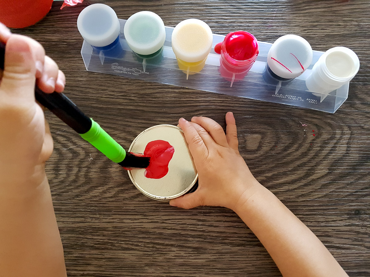 toddler painting a jar lid