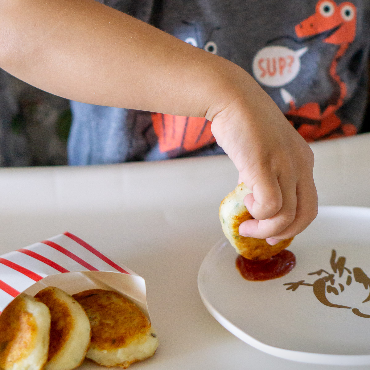 toddler dipping potato nugget in ketchup