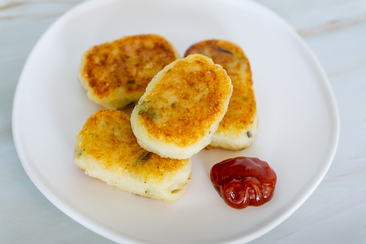 mashed potato nuggets on a plate with ketchup