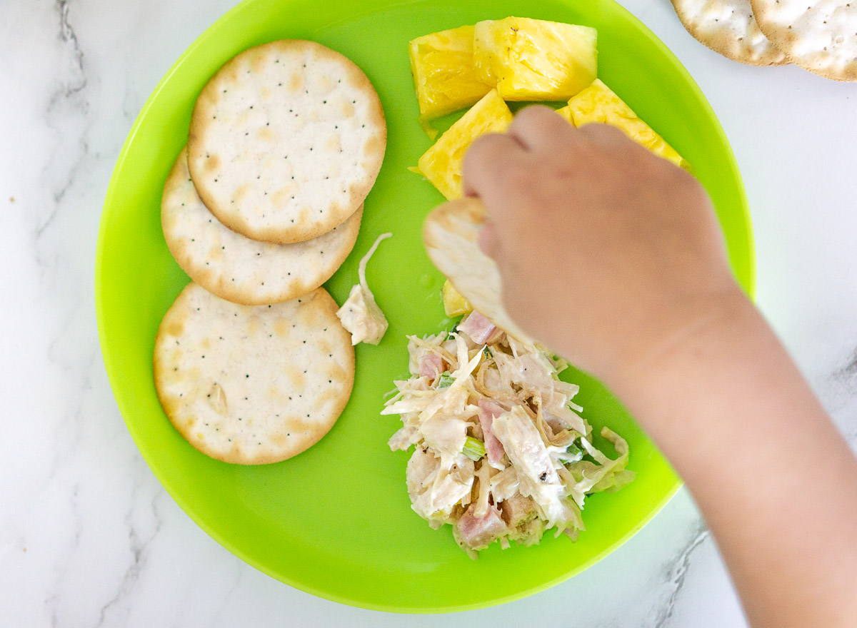 toddler eating Hawaiian chicken salad with pineapple