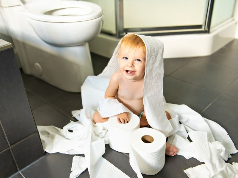 toddler playing with toilet paper