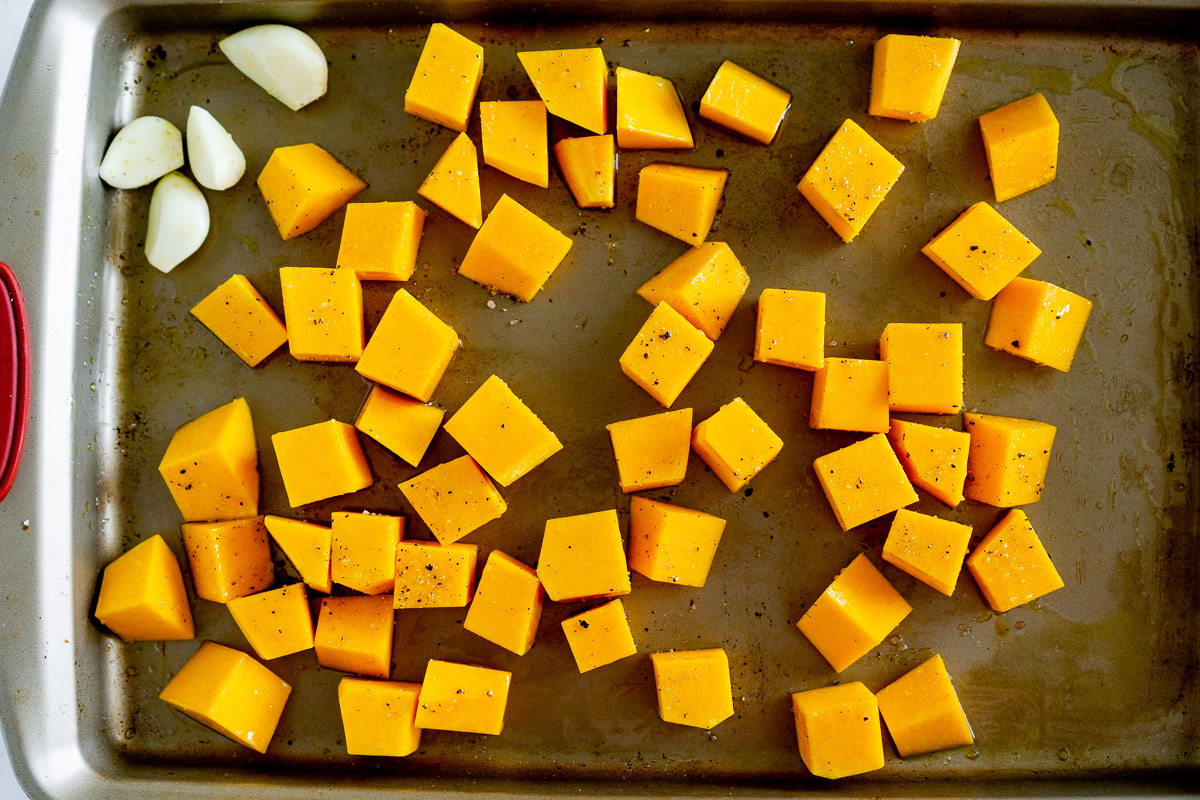 cubed butternut squash and garlic on a baking sheet