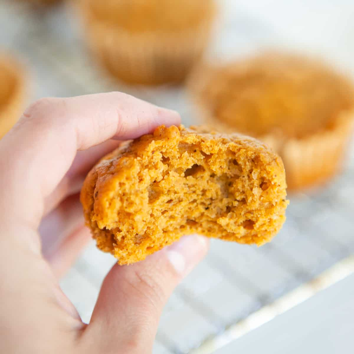hand holding pumpkin muffin cut in half to show the texture of the inside