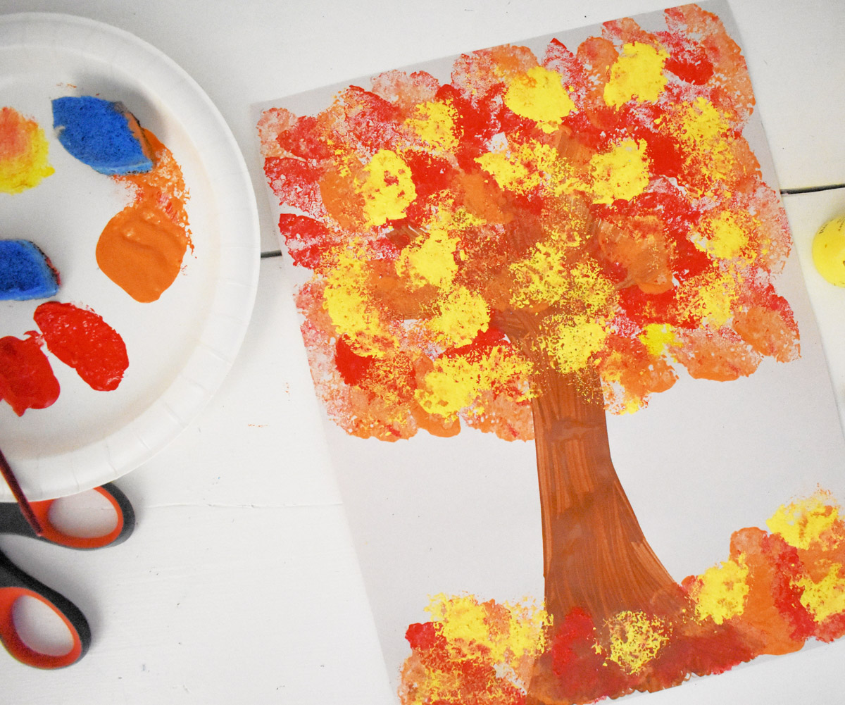 sponge stamped tree next to paper plate with finger paints and scissors - a Fall craft for toddlers