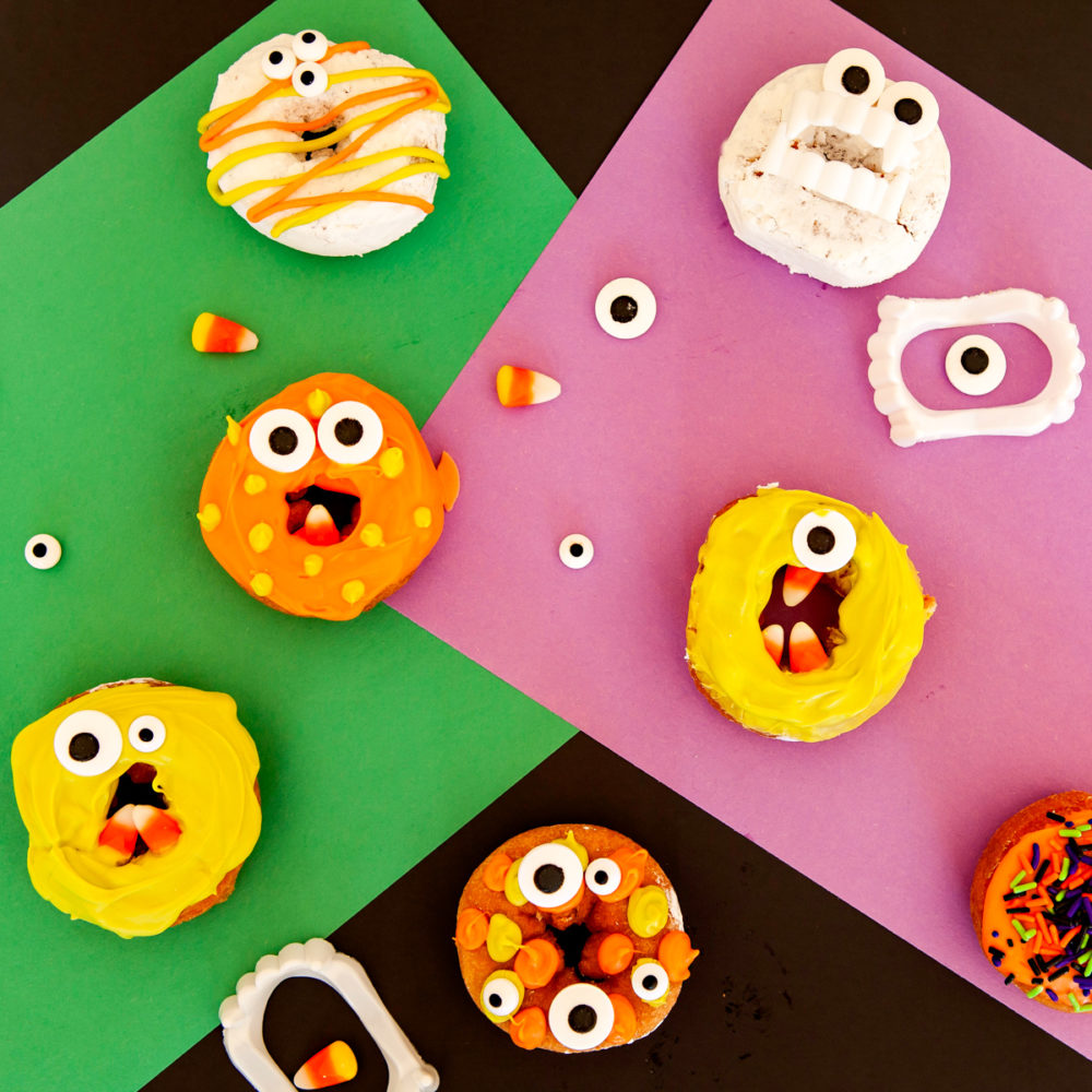 overhead image of Halloween decorated donuts - monster donuts on colorful construction paper
