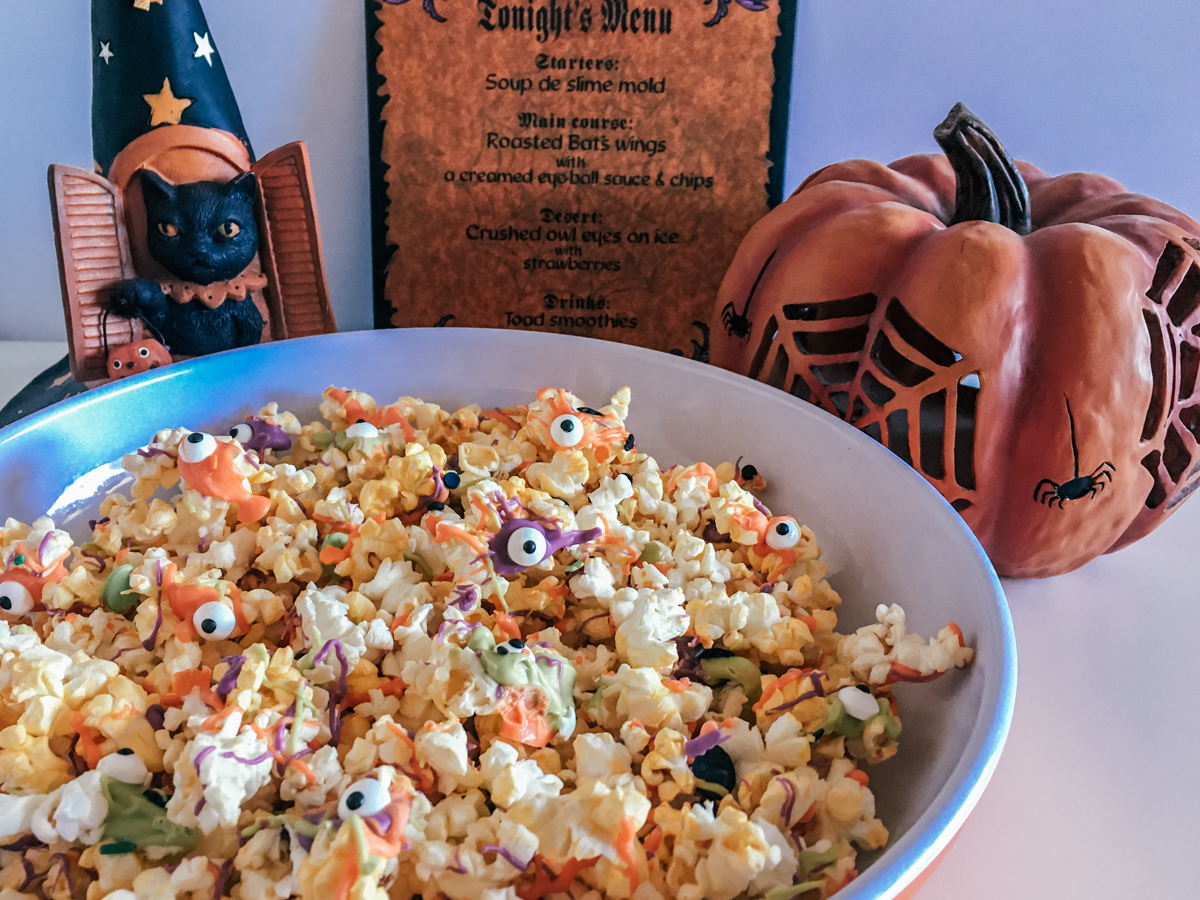 bowl of Monster Popcorn for a Halloween party next to Halloween decorations