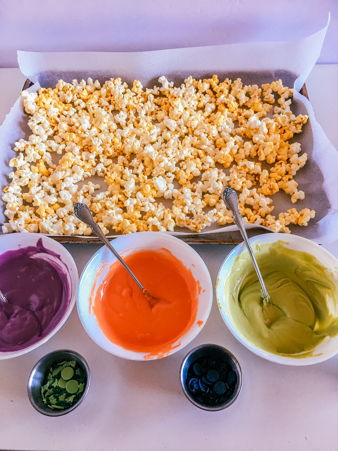 popped popcorn and halloween colored candy melts melted in bowls