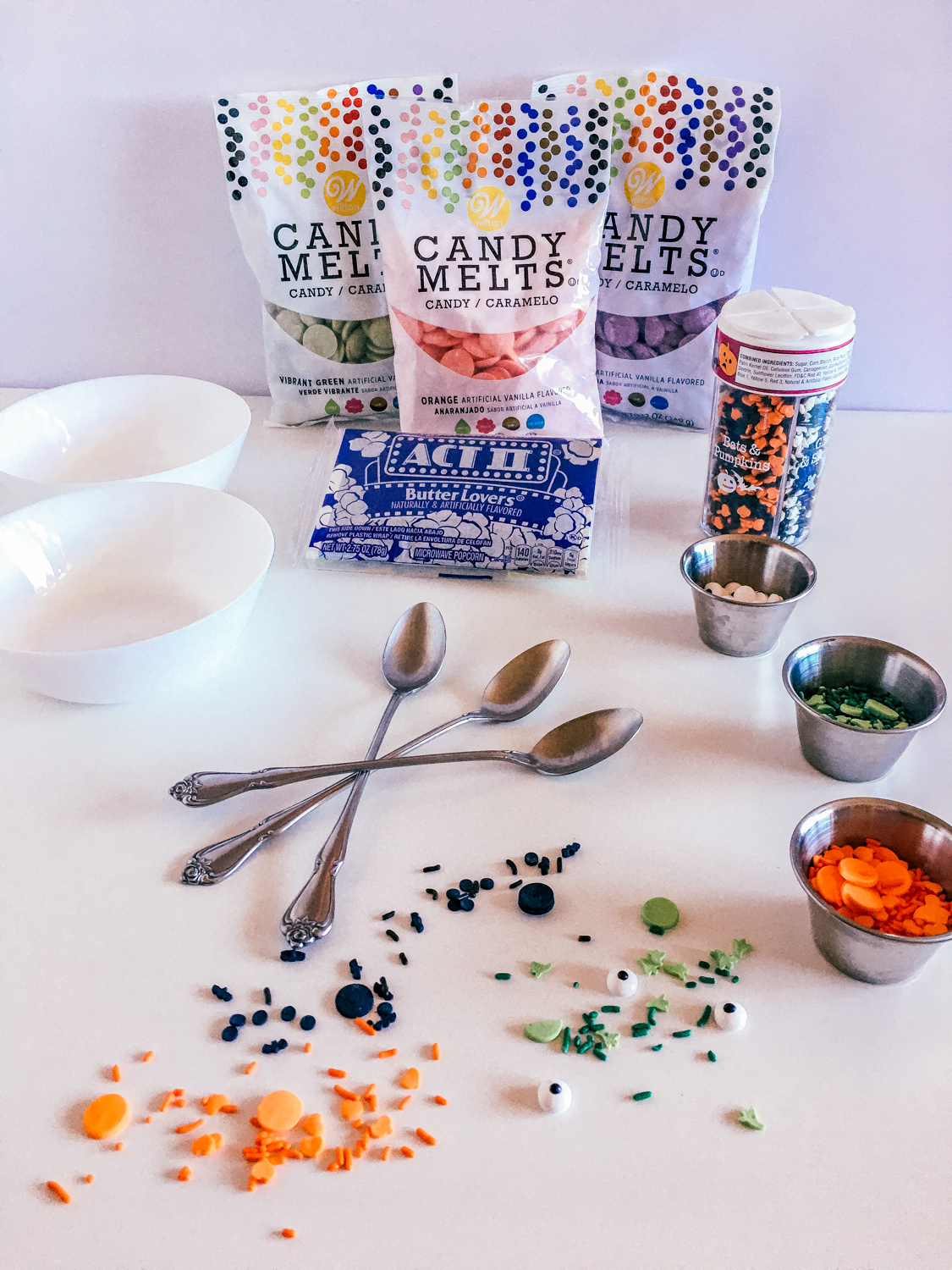 ingredients to make halloween popcorn - candy melts, popcorn bag, halloween sprinkles