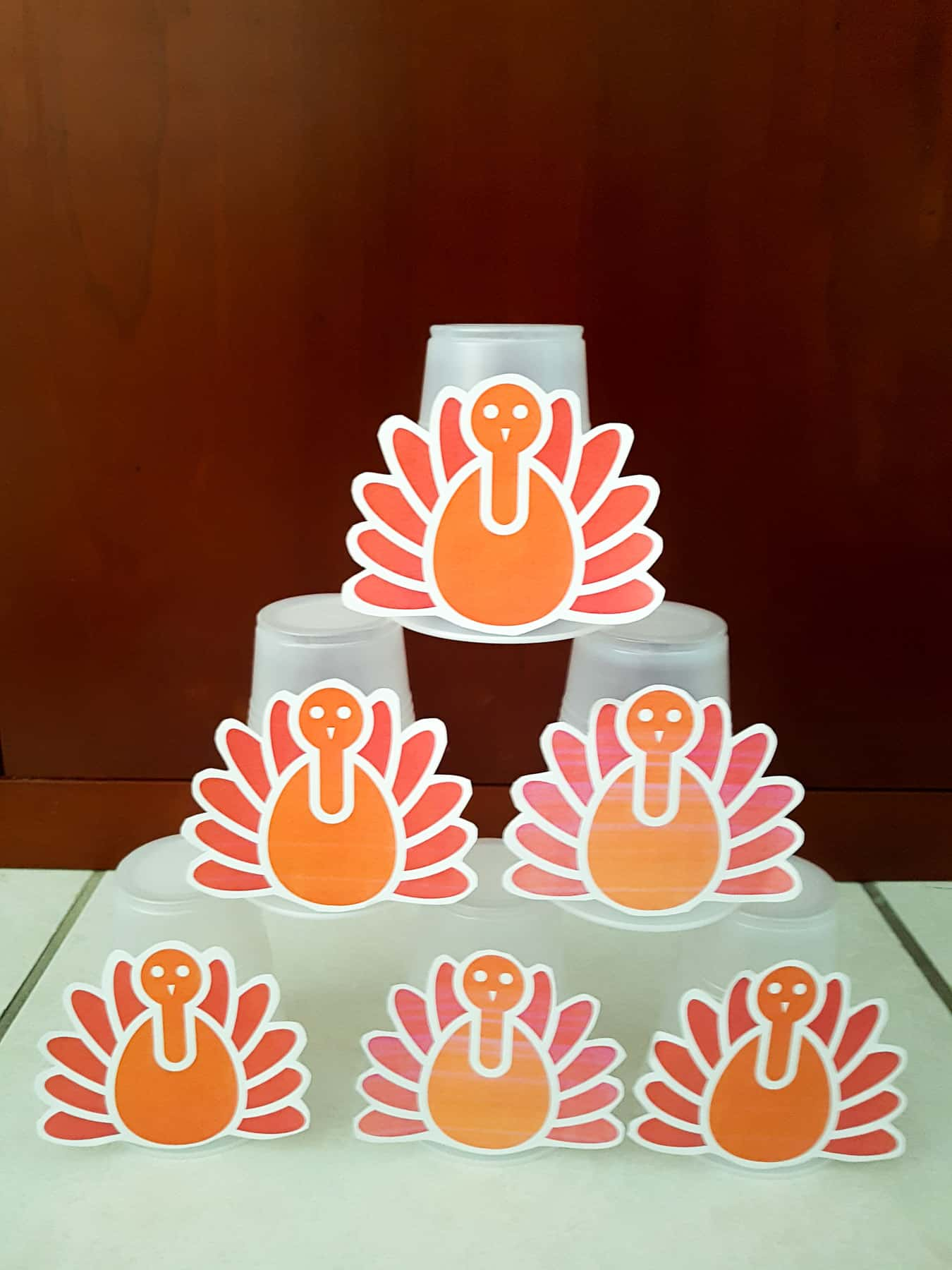 plastic cups with paper thanksgiving turkeys glued to them stacked as a pyramid, to demonstrate a toddler thanksgiving bowling activity