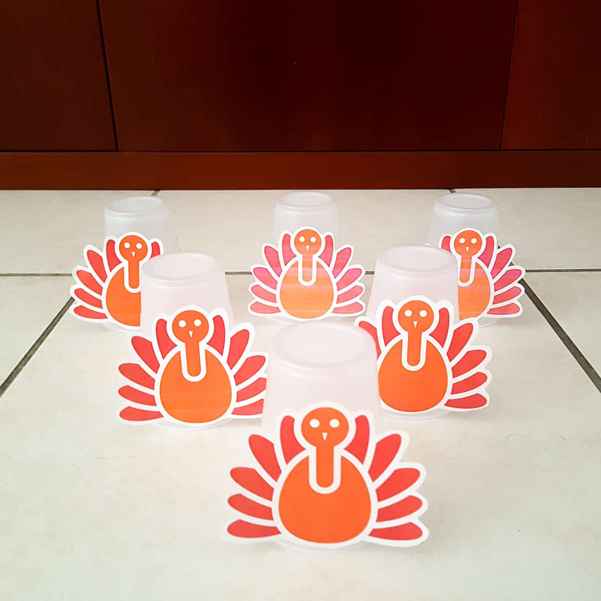 plastic cups with paper thanksgiving turkeys glued to them lined up like bowling pins to demonstrate a toddler thanksgiving bowling activity