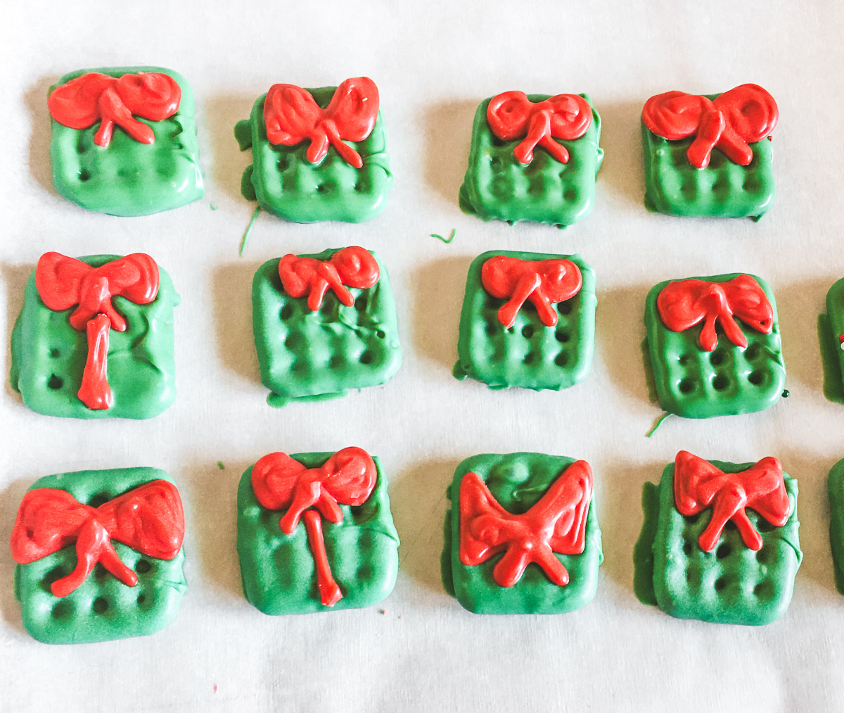 Christmas pretzels decorated like gift boxes with bows laying on parchment paper drying