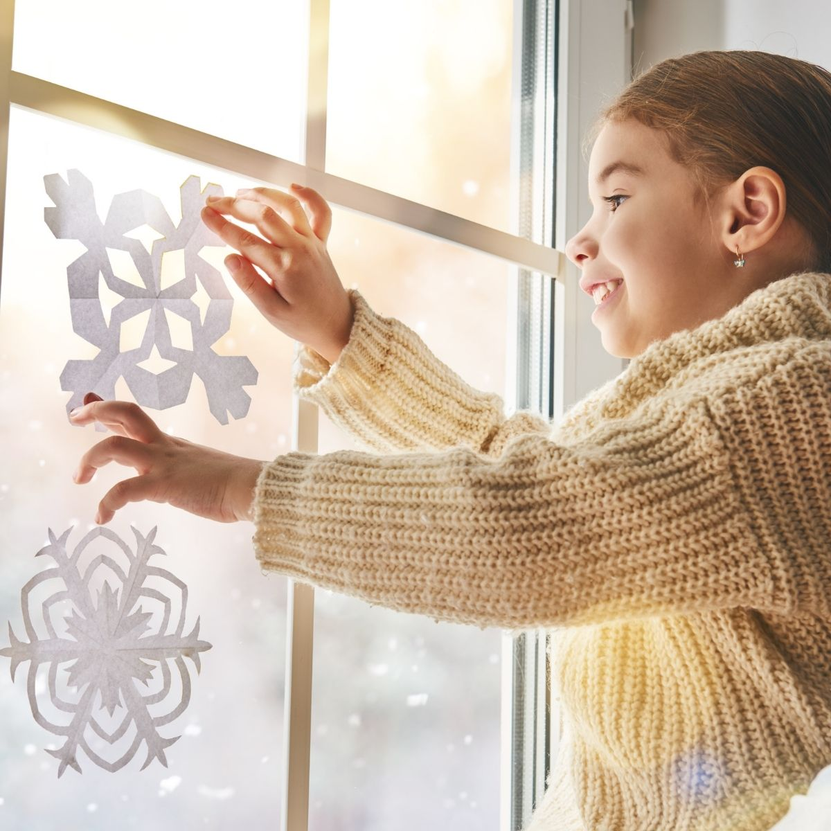 girl taping snowflakes to her window