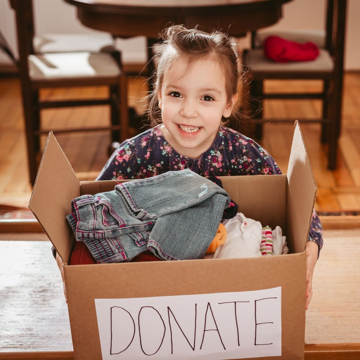 girl holding box of clothes for donation