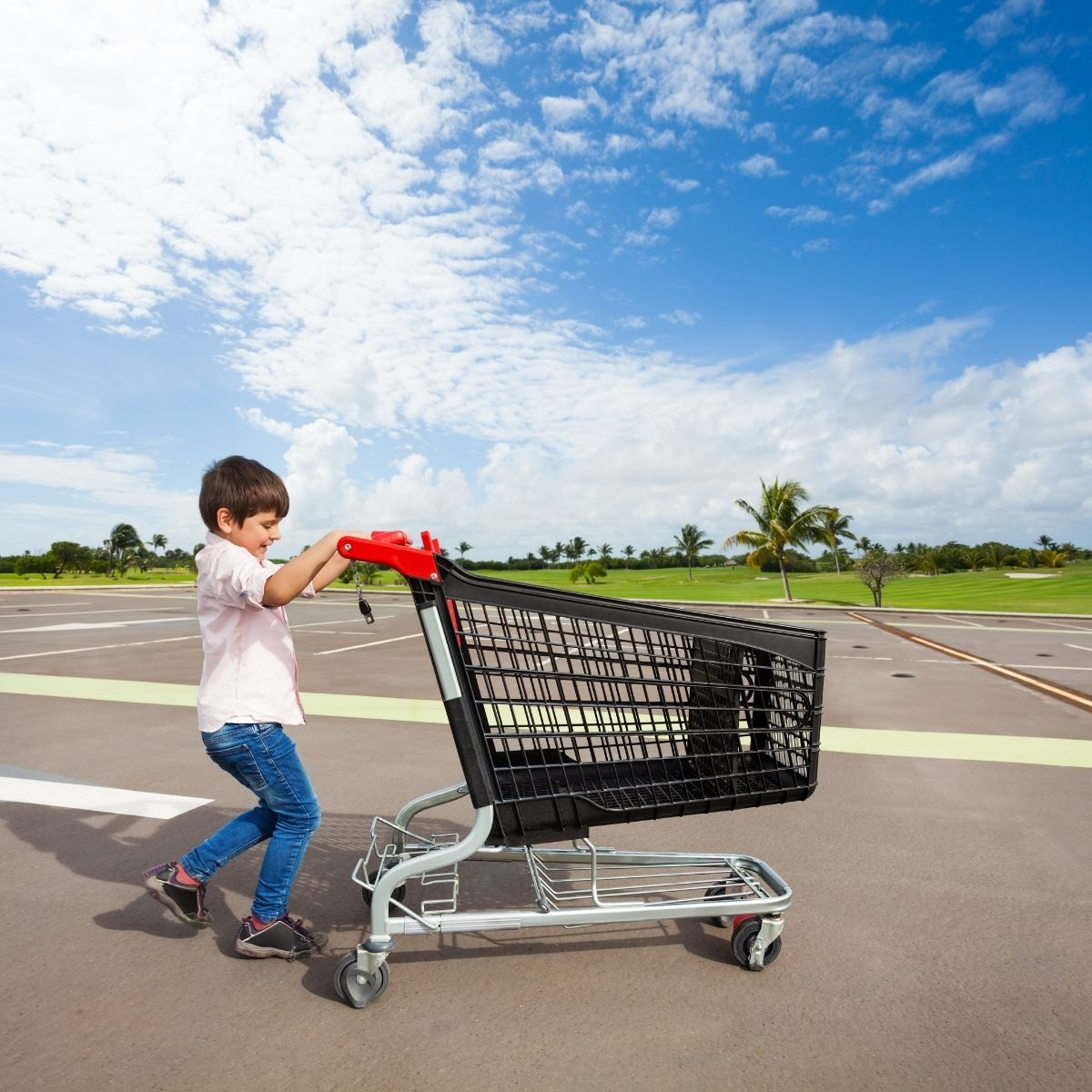 boy returning shopping cart in a parking lot