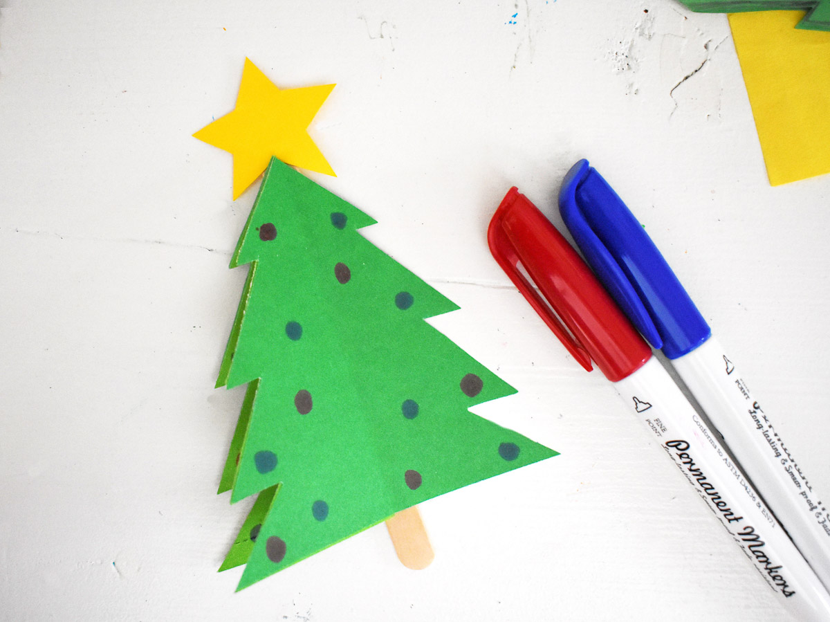 paper craft christmas tree craft next to markers and supplies