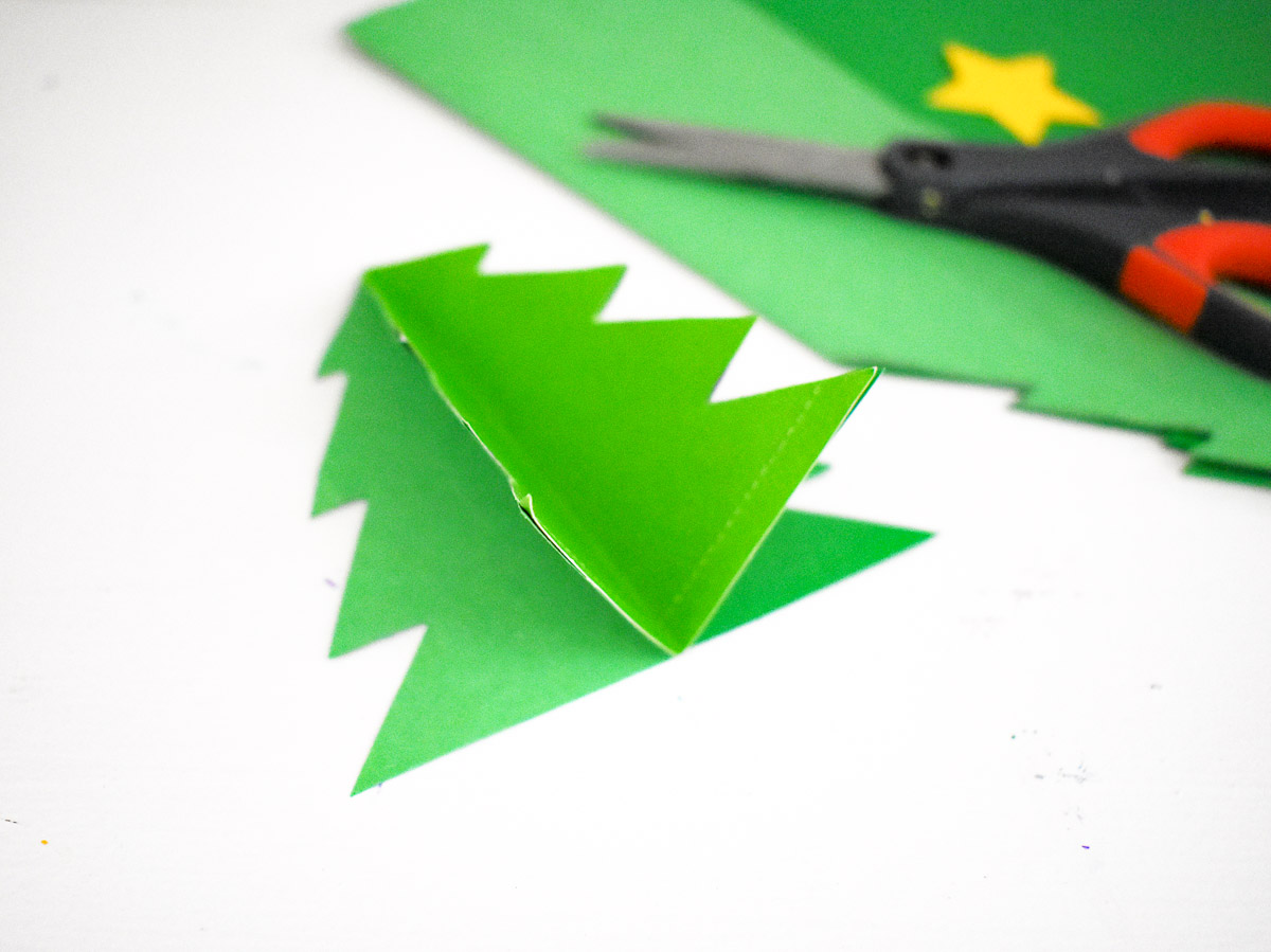 folded paper christmas tree next to scissors