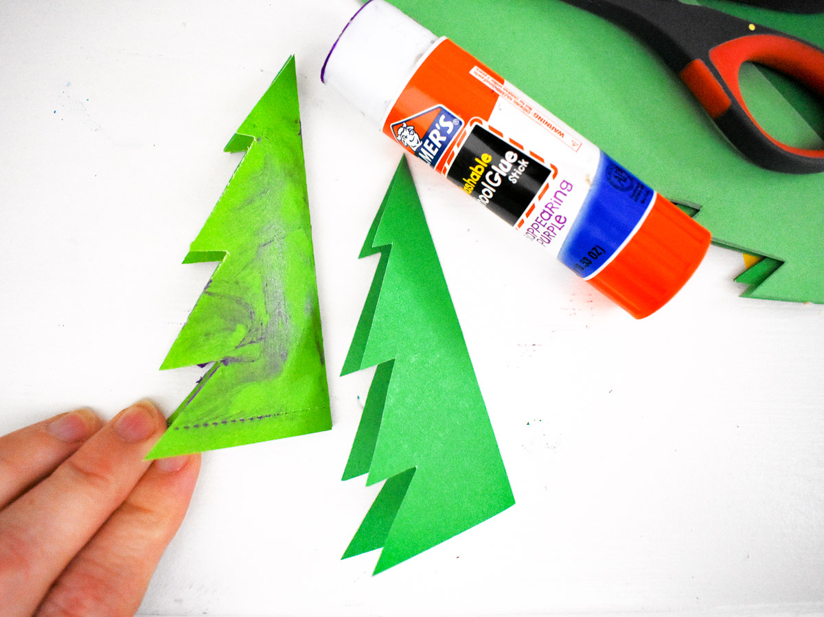 2 paper christmas trees and a glue stick to make a christmas tree craft