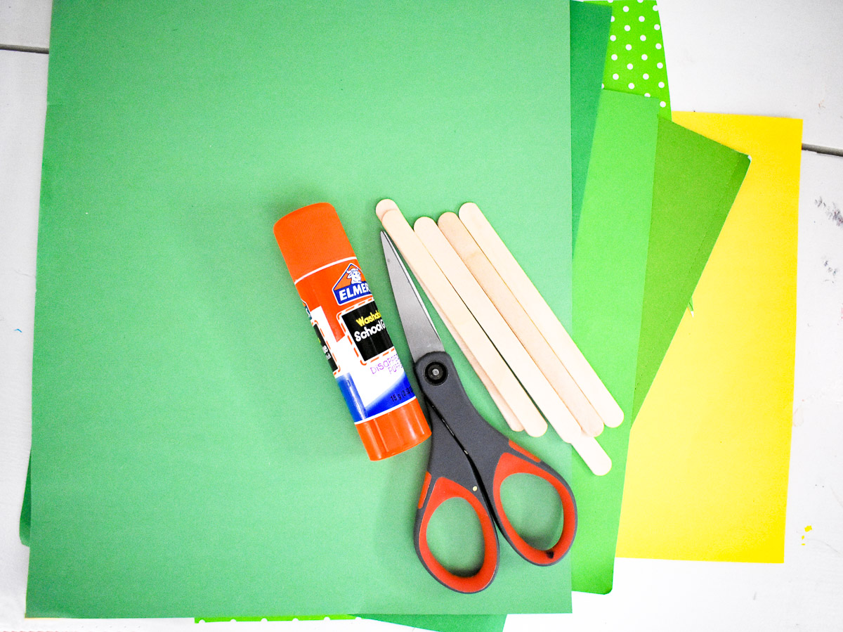 supplies to make a paper christmas tree craft with toddlers: cardstock, scissors, glue stick, craft sticks