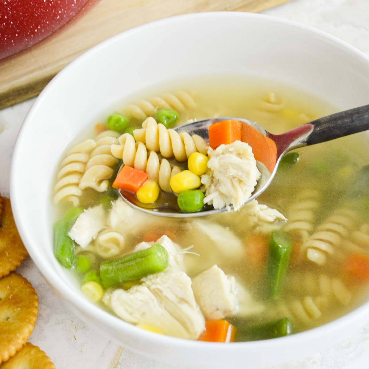 Spoon of chicken noodle soup with vegetables