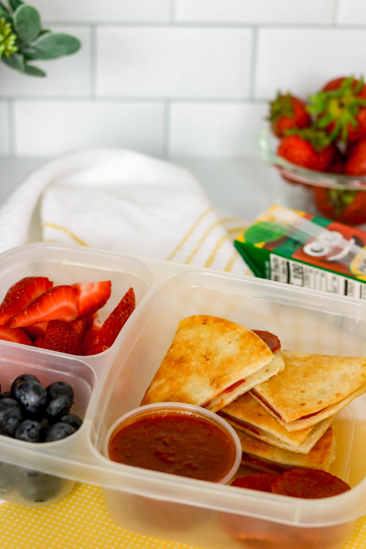 Pepperoni pizzadillas packed for a kid's lunch in a bento box with berries.