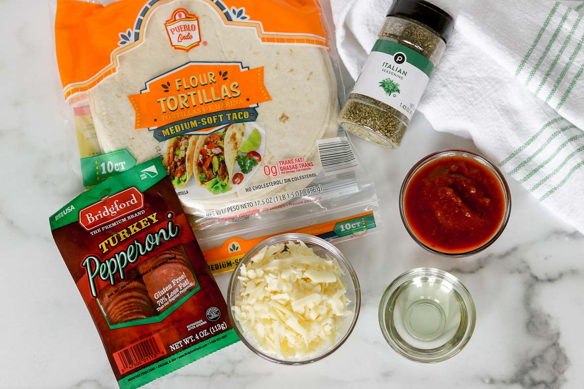 Ingredients to make pepperoni pizzadillas: tortillas, shredded cheese, Italian seasoning, pepperoni slices, and marinara sauce.