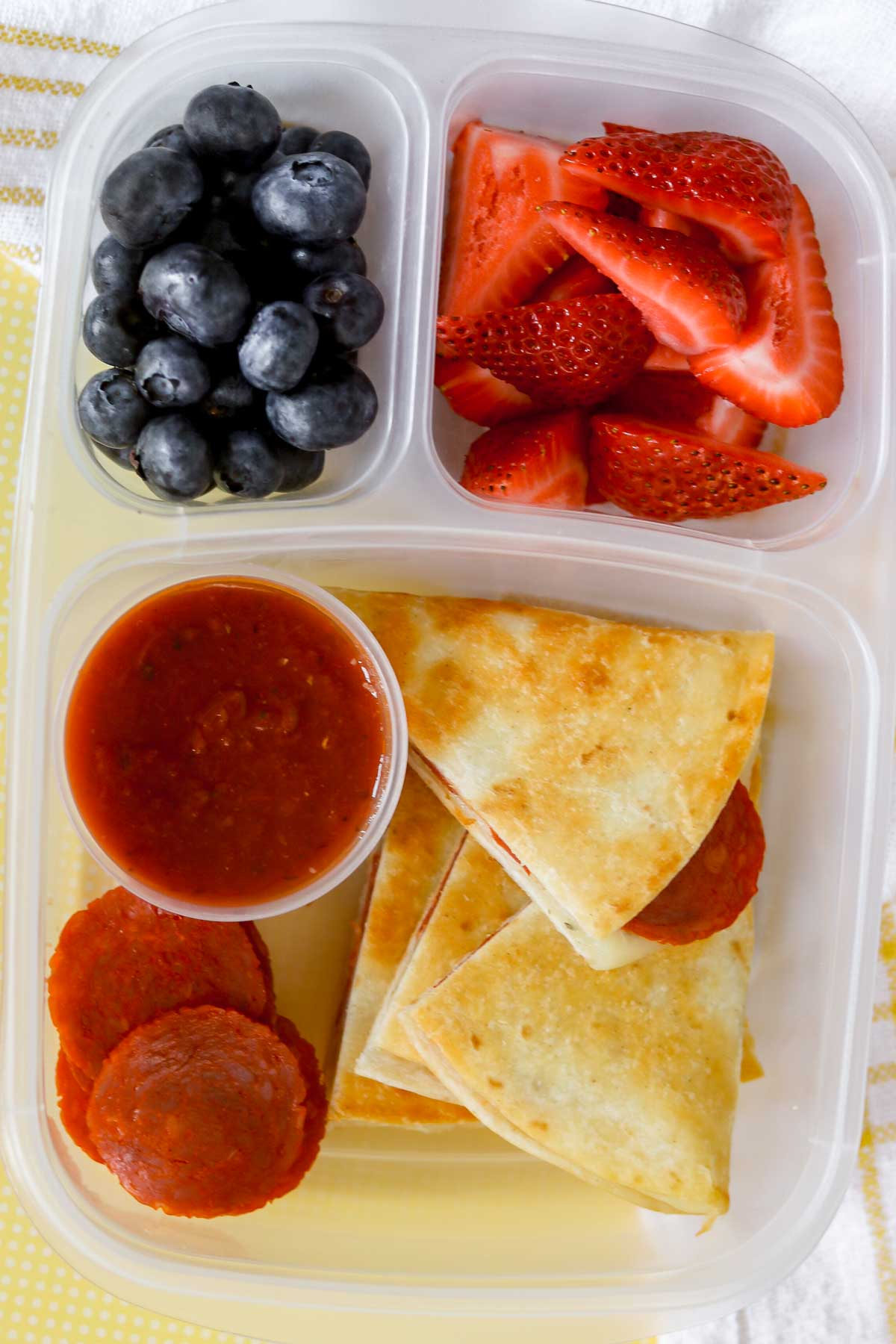 Pepperoni pizza quesadillas in a lunch container with strawberries and blueberries.