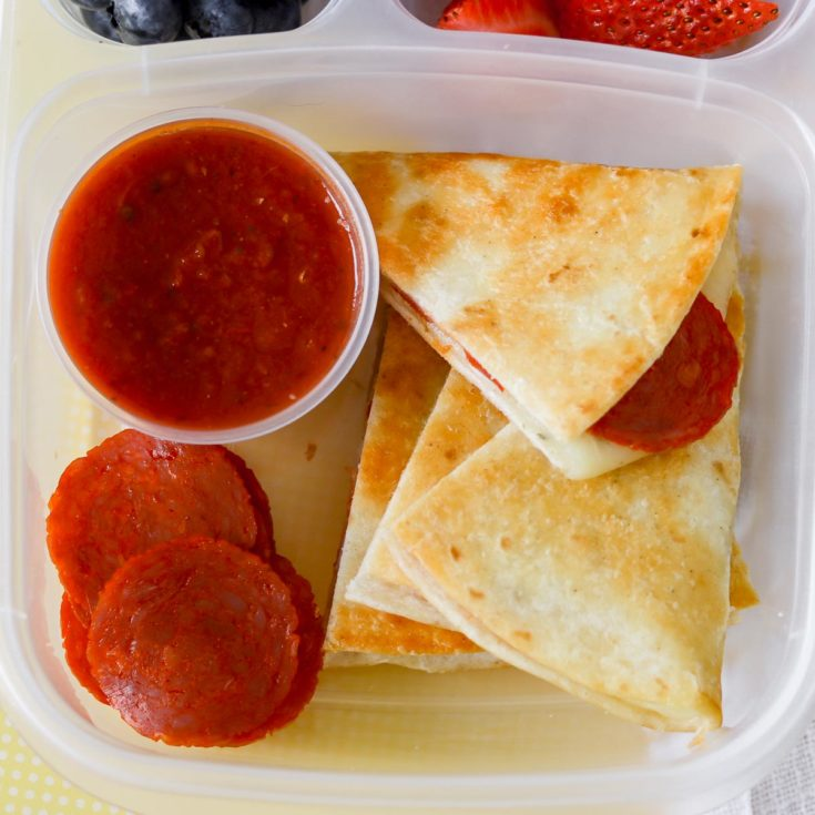 Pepperoni pizzadillas with pizza sauce in a lunch container.