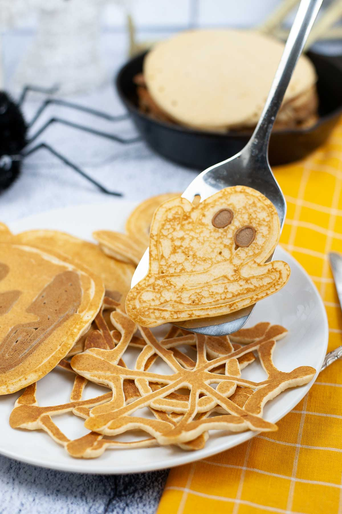 Spatula holding up ghost shaped pancake with other Halloween pancakes on a plate and Halloween decorations.