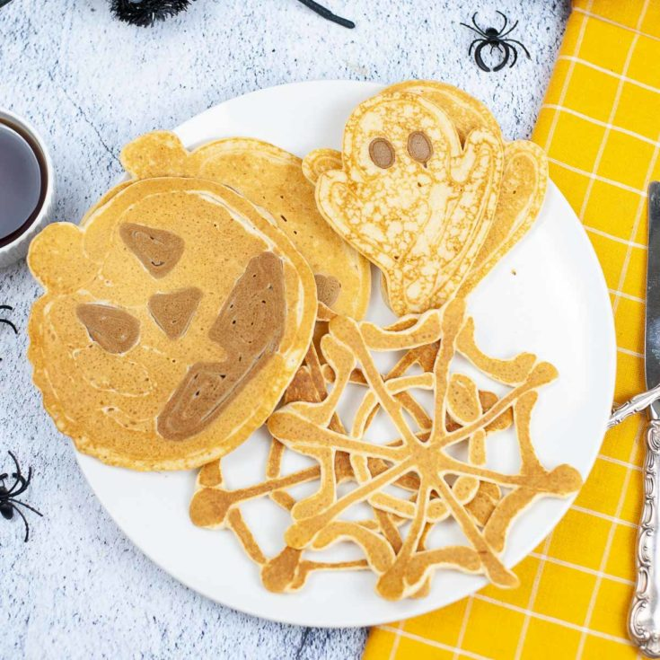 A plate with a spider web pancake, a Jack o lantern pancake, and a ghost pancake for Halloween breakfast.